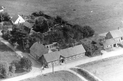 Forgrund: Staksrode Brugsforening. Til højre smedjen og centralen, bagved mellem træerne skolen og i baggrunden Den Gamle Skole ca. 1955.