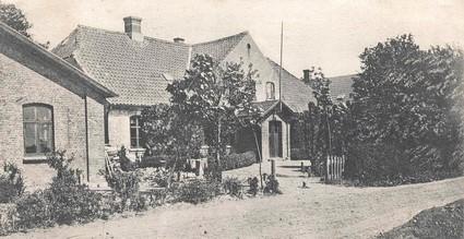 Vrigsted Højskole med en for længst nedrevet bygning i forgrunden. Den skal over tid have rummet både forsamlingshus, gymnastikhus, håndværkerafdeling og friskole, ca. 1900.